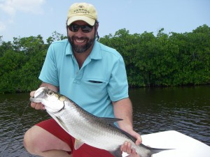 "The author holds a ""baby"" tarpon taken from one of the cenote-fed saltwater lakes near the southern end of the Yucatan Peninsula."