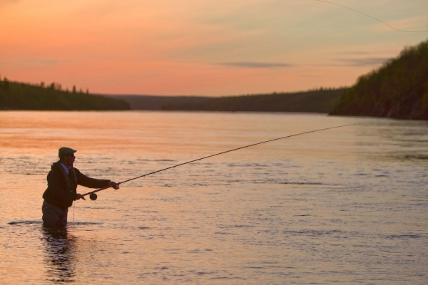 An angler unfurls a spey cast in low light on the Ponoi.