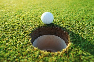 Golf Ball Sitting on Edge of Hole