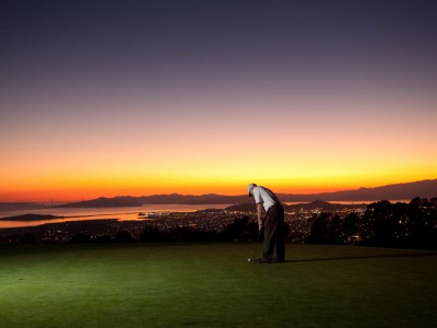 Berkeley Country Club's putting green at dusk, with the San Francisco Bay lit by the setting sun.