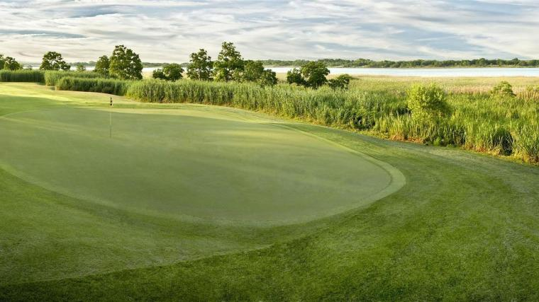 The small green at the 14th, a short par-4 running along the Savannah River, slopes right to left toward the marsh.