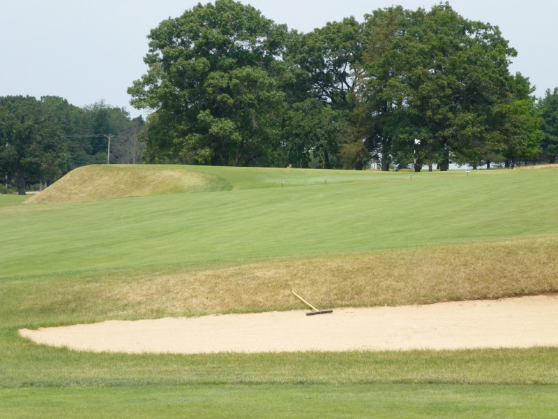 The left side of the 1st green drops away over 10 feet into a bunker, a motif that will be repeated on nearly every hole.