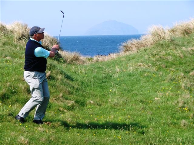 Alistair Nicol plays a shot with a faint Ailsa Craig in the distance