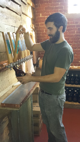 Christophe Gagné fills a growler at the new Hermit Thrush Brewery in Brattleboro, Vermont