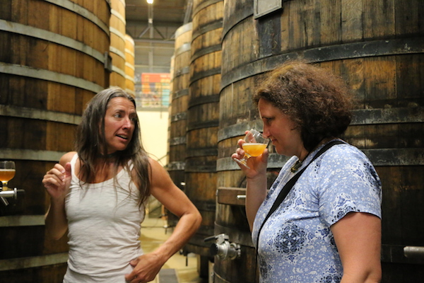 New Belgium blender Lauren Salazar (left) sampling sour beer in the wood cellar with Anne-Françoise Pypaert (photo from NB website)