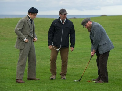 Director Jason Connery gives old time putting tips to his principals.