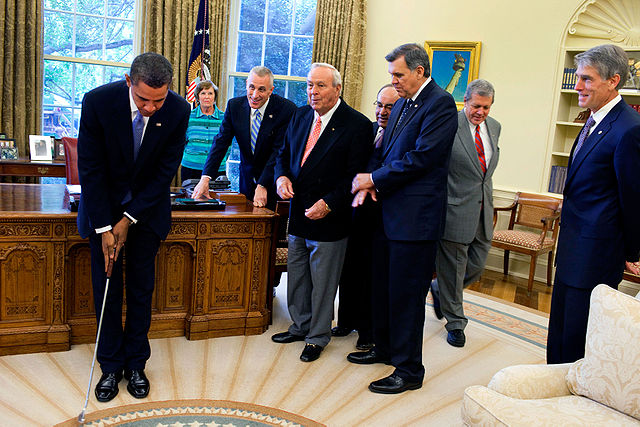 President Barack Obama takes a practice putt with a golf club presented to him by golf legend Arnold Palmer prior to the signing ceremony for H.R. 1243, the Arnold Palmer Congressional Gold Medal Act, in the Oval Office, Sept. 30, 2009