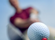 worm's eye view of a golfer about to hit a golf ball with iron
